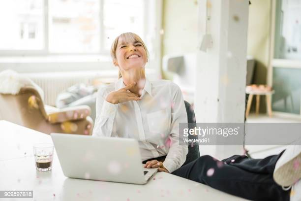 confetti falling on businesswoman with laptop in office - freude stock-fotos und bilder