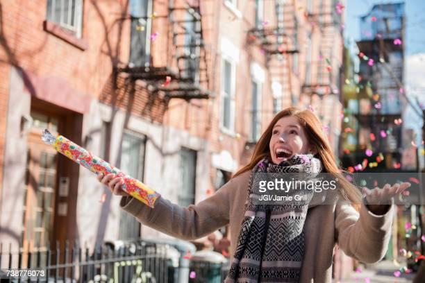 Confetti falling on Caucasian woman wearing scarf