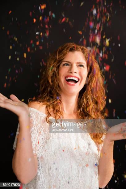 Confetti falling on celebrating Caucasian woman