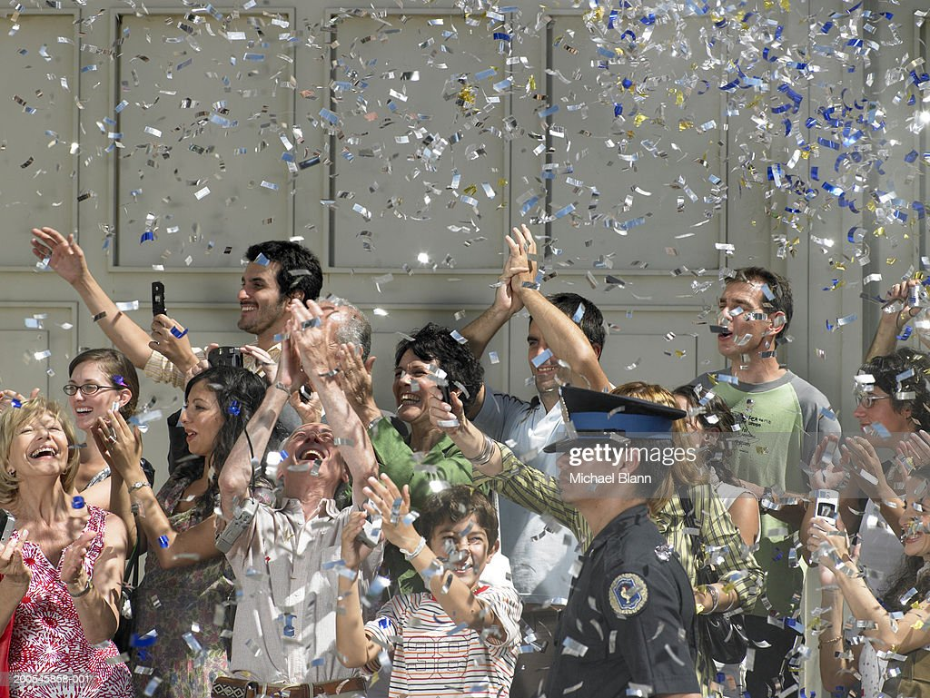 Confetti falling on crowd cheering in street : Stock Photo