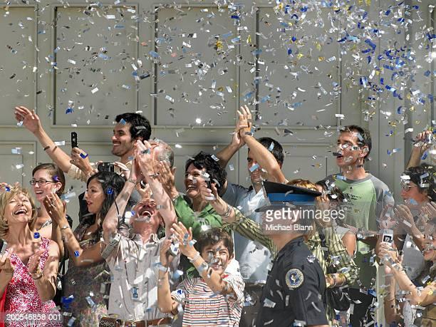 Confetti falling on crowd cheering in street