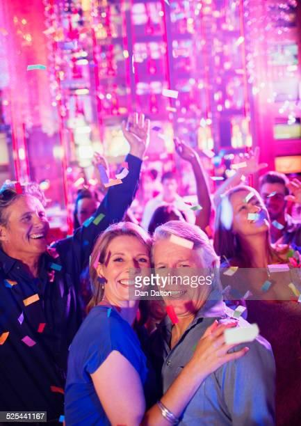 Confetti falling on smiling mature people dancing in nightclub