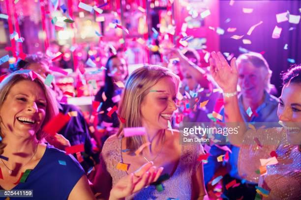 Confetti falling on smiling mature women dancing in nightclub
