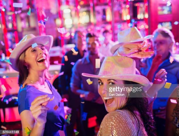 Confetti falling on women wearing cowboy hats laughing and dancing in nightclub
