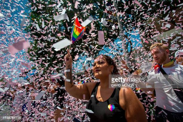 Confetti falls around a spectator at the annual LA Pride Parade in West Hollywood, California, on June 9, 2019. - LA Pride began on June 28 exactly...