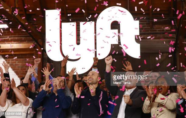 Confetti falls as Lyft CEO Logan Green and President John Zimmer ring the Nasdaq opening bell celebrating the company's initial public offering on...