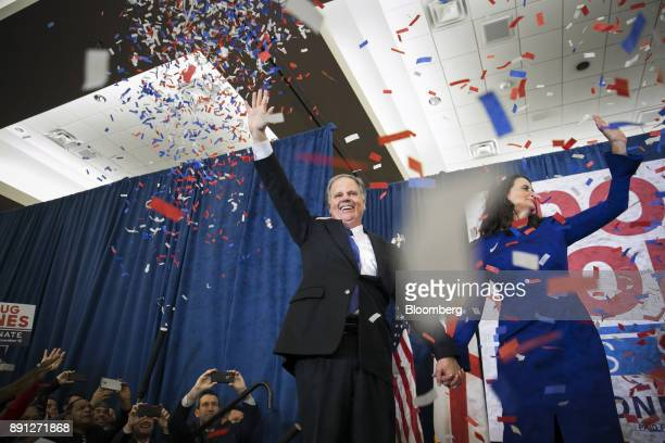 Confetti falls as Senatorelect Doug Jones a Democrat from Alabama center and wife Louise Jones wave to the audience at an election night party in...