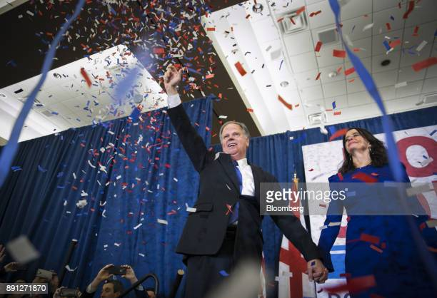 Confetti falls as Senatorelect Doug Jones a Democrat from Alabama center and wife Louise Jones greet the audience at an election night party in...