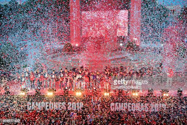 TOPSHOT Confetti falls on Atletico Madrid's players as they raise their trophy in front of supporters during celebrations for their Europa League...