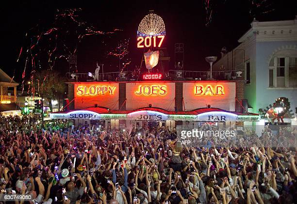 Confetti flies and New Year's Eve revelers celebrate after a giant replica of a conch shell descended to the roof of Sloppy Joe's Bar in Key West,...