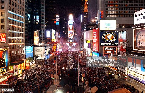 Confetti flies in the air above the crowd gathered in Times Square as the ball drops above One Times Square to signal the start of the New Year 01...