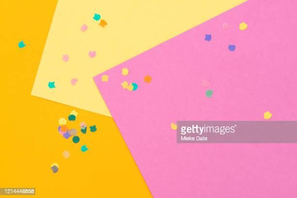 confetti op gekleurde achtergrond - gekleurde achtergrond stock pictures, royalty-free photos & images