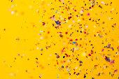 Confetti rain on yellow background