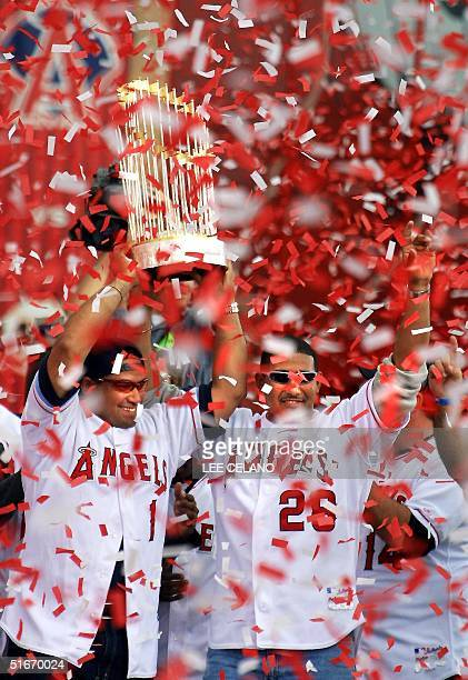 Confetti showers World Series Champion Anaheim Angels' catchers Bengie Molina and Jose Molina hold aloft the championship trophy as at the close of a...