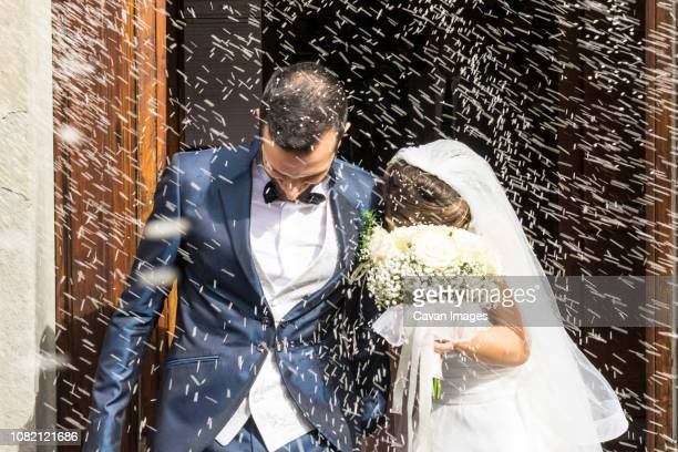 confetti throwing on happy newlywed couple leaving from church - church wedding decorations stock pictures, royalty-free photos & images