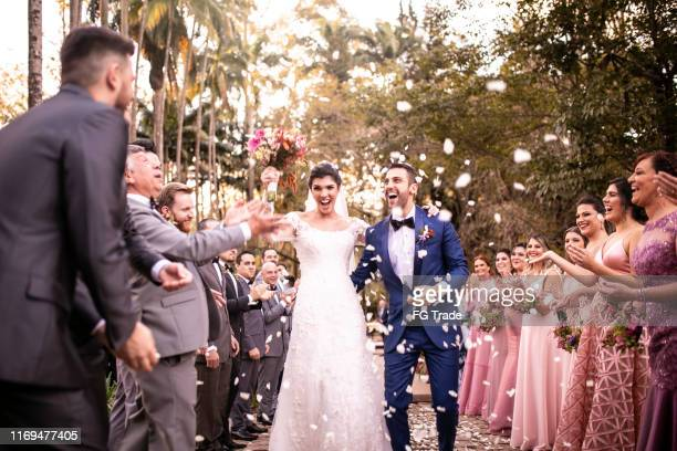 confetti throwing on happy newlywed couple - wedding stock pictures, royalty-free photos & images