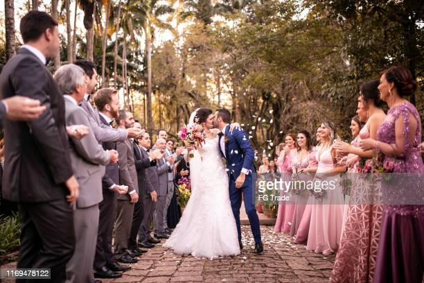 confetti throwing on happy newlywed couple - matrimonio foto e immagini stock