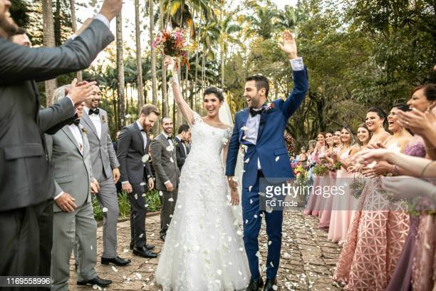 confetti throwing on happy newlywed couple - wedding ceremony stock pictures, royalty-free photos & images
