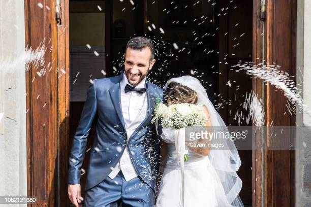 confetti throwing on happy newlywed couple standing at church entrance - trouwen stockfoto's en -beelden