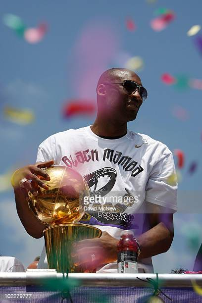 Confetti thrown from the crowd falls around Los Angeles Lakers guard Kobe Bryant as he holds the championship trophy while riding in the victory...