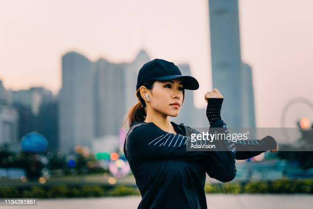 confidence and determined asian sports woman stretching arms outdoors against urban city skyline - cap hat stock pictures, royalty-free photos & images