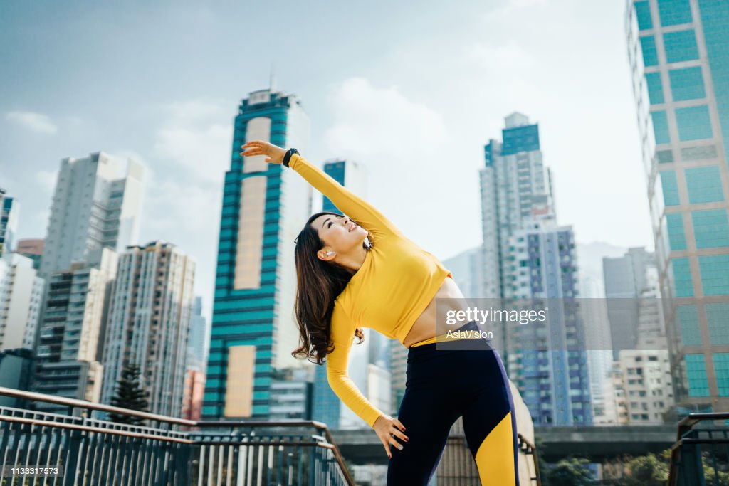 Confidence and determined sports woman stretching arms outdoors against urban cityscape : Stock Photo