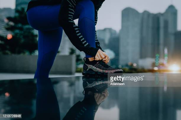 confidence and energetic sports woman tying shoe laces and getting ready to exercise in urban park against city skyline at sunset - motivation stock pictures, royalty-free photos & images