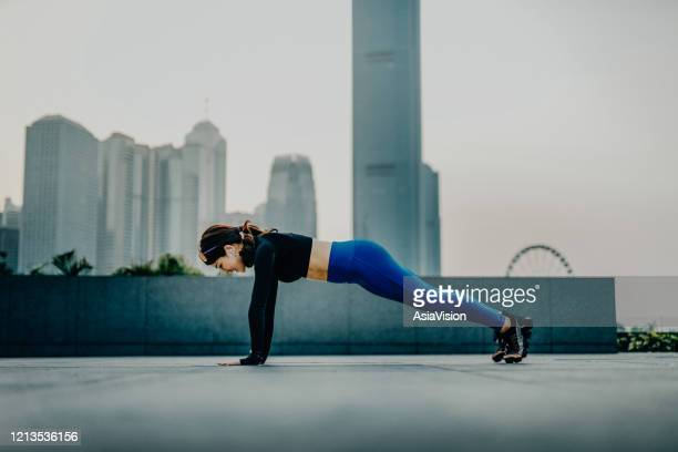 confidence and energetic young asian sports woman exercising and working out outdoors in urban park against city skyline at sunset - self improvement stock pictures, royalty-free photos & images