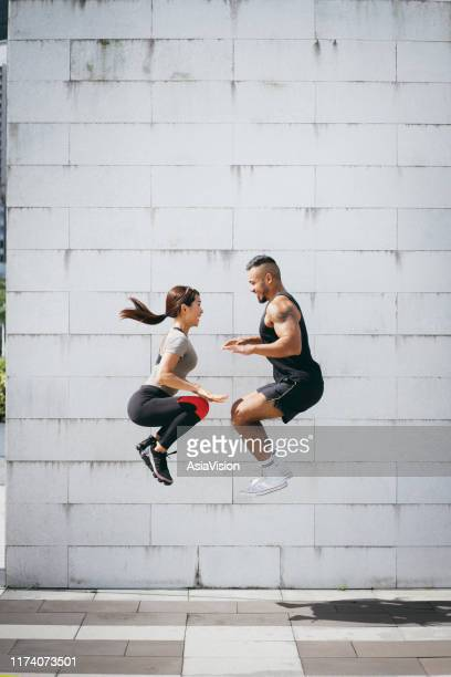 confidence and energetic young sporty couple exercising and jumping high up together outdoors at city park in the morning - taking a shot sport stock pictures, royalty-free photos & images