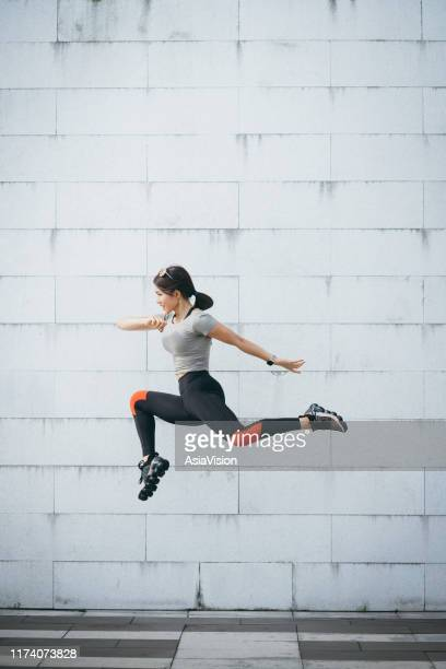 confidence and energetic young sporty woman jumping in air against grey wall at city park - jumping stock pictures, royalty-free photos & images