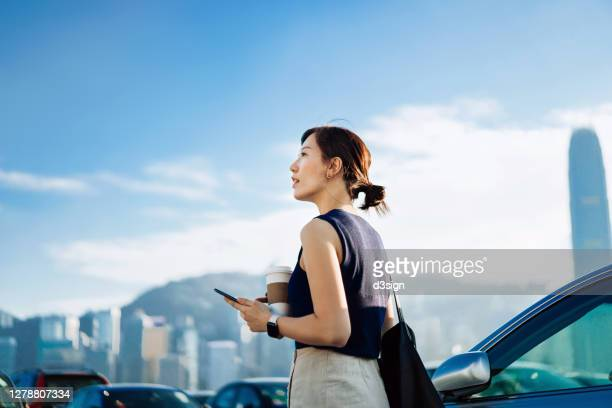 confidence and professional young asian businesswoman walking out of her car, holding smartphone and a cup of coffee. looking towards the sky against urban cityscape. business on the go concept - smart watch stock pictures, royalty-free photos & images