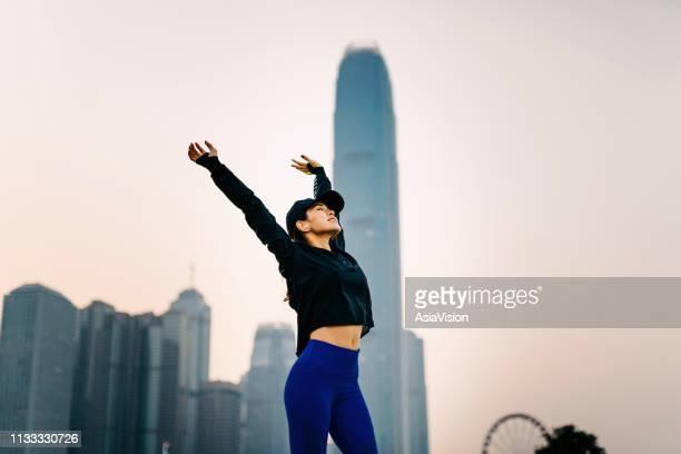 自信と笑顔アジアのスポーツ女性が日没時の都市の街並みに対して屋外で腕の頭上を伸ばす - 息を止める ストックフォトと画像