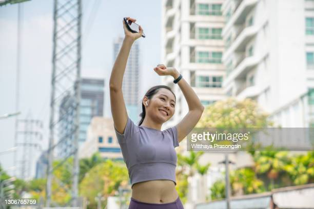 confidence and smiling asian sports woman stretching arms overhead outdoors against urban cityscape at sunset - 息を止める ストックフォトと画像