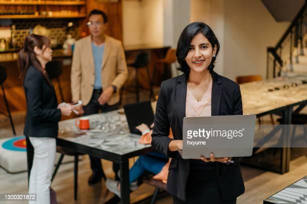 vertrouwen indische onderneemster die laptop in co-working ruimte met behulp van - oprichter stockfoto's en -beelden