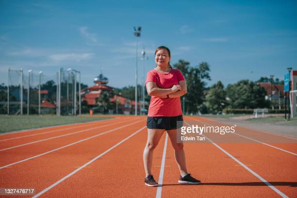 confidence satisfied body positive female athlete arms crossed looking at camera smiling standing on all-weather-track and field stadium in the morning - forward athlete stock pictures, royalty-free photos & images