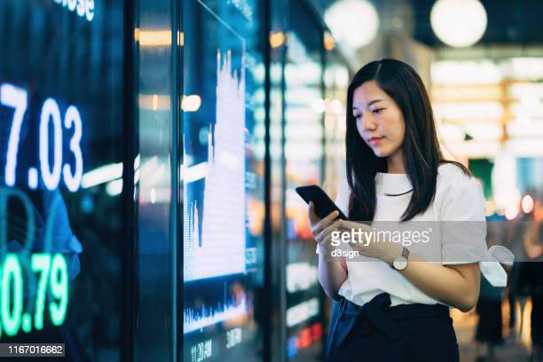 confidence young asian businesswoman checking financial trading data on smartphone by the stock exchange market display screen board in downtown financial district - business finance and industry stock pictures, royalty-free photos & images