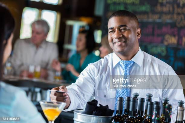 Confident African American bartender hands credit card to customer