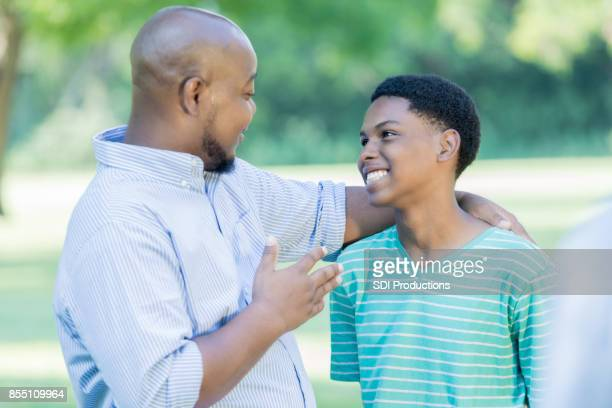 Confident African American dad gives teenage son advice