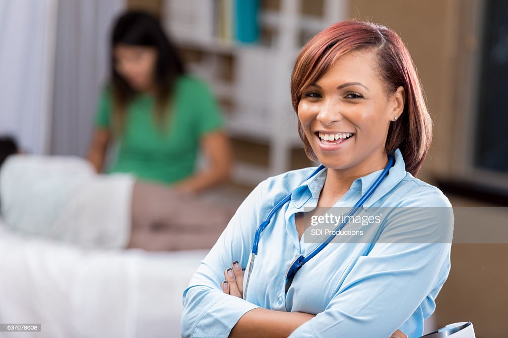 Confident African American Female Emergency Room Physician In Exam ...