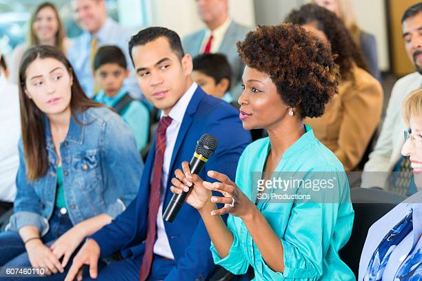confident african american woman asks question during a meeting - town hall meeting stock photos and pictures