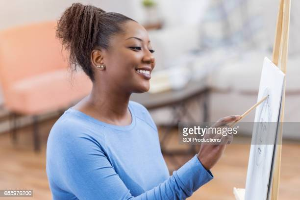 Confident African American woman works on sketch in a studio