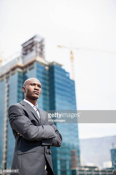Confident african businessman with cityscape.