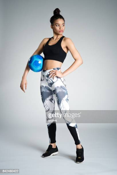 Confident afro american young woman in sports wear holding ball