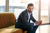 Confident and concentrated. Thoughtful handsome businessman is thinking while sitting in his modern office about business concept while sitting on sofa