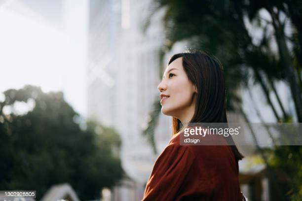 confident and determined young asian businesswoman looking away hopefully, standing against contemporary corporate skyscrapers in central business district in the city. female leadership and determined to success - business strategy stock pictures, royalty-free photos & images