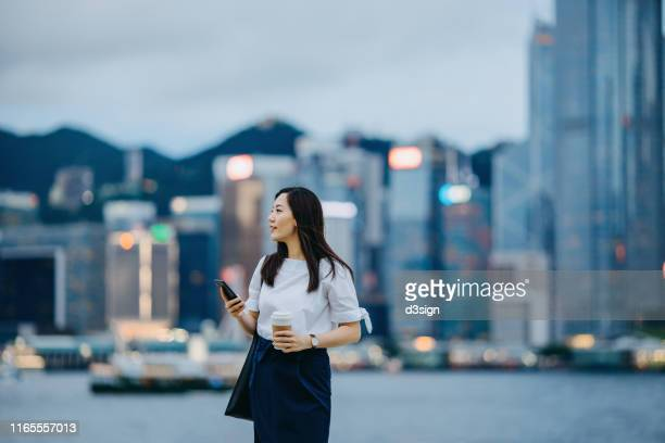 confident and smiling young businesswoman with smartphone in financial district, against illuminated corporate skyscrapers at dusk - financiën en economie stockfoto's en -beelden