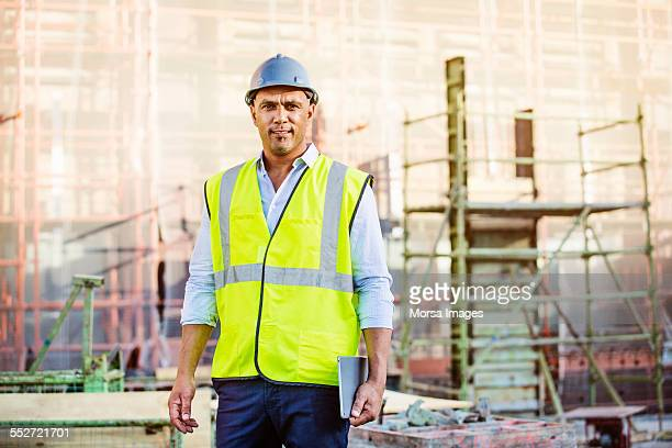 Confident architect holding digital tablet at site