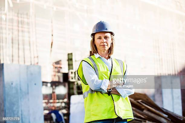 Confident architect standing arms crossed at site