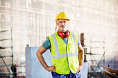 Confident architect standing at construction site
