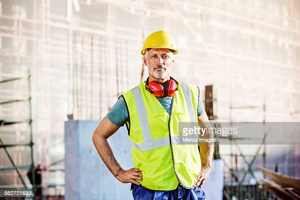 confident architect standing at construction site - industrie du bâtiment photos et images de collection